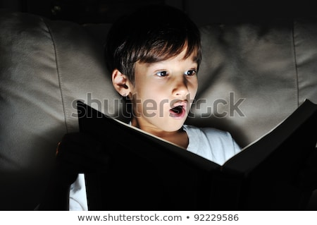 Shocked kid reading book, light in darkness Stock photo © zurijeta