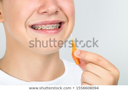 Happy man holding toothbrush on gray background Stock photo © deandrobot