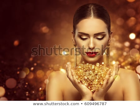 close up of beautiful woman face with gold earring Stock photo © dolgachov