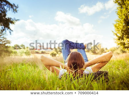 girl lying on grass looking at sky stock photo © is2