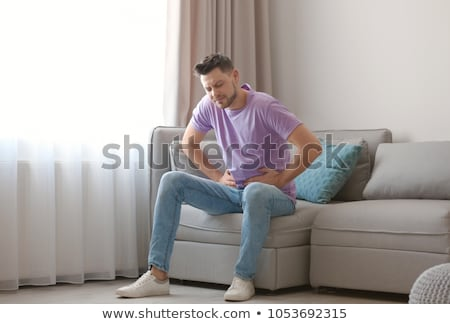 unhappy man suffering from stomach ache Stock photo © dolgachov