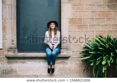 Genç kadın oturma taş duvar kamera kadın pembe Stok fotoğraf © IS2