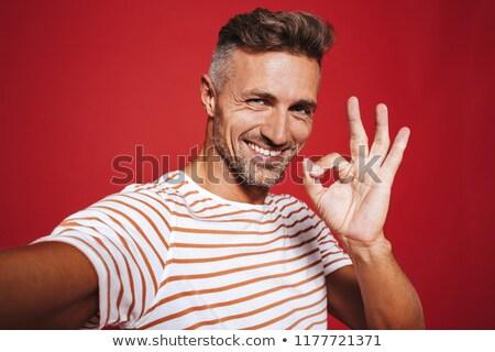 Brunette jonge man gestreept tshirt glimlachend tonen Stockfoto © deandrobot