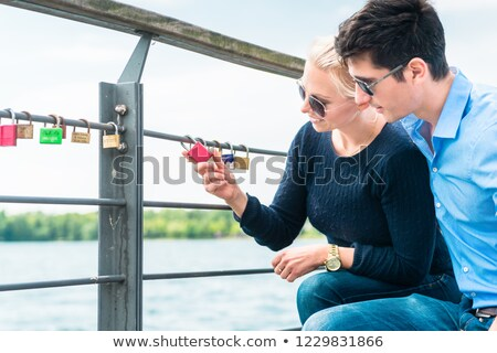 Young couple looking at padlock hang on railing Stock photo © Kzenon