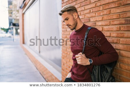 Smiling casual man carrying backpack at the city street Stock photo © deandrobot
