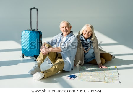 Smiling senior woman with suitcase and passport. Stock photo © NeonShot