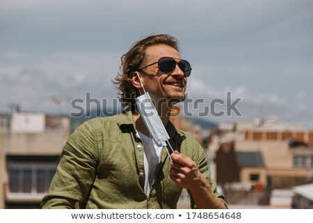 man with sunglasses holding his hand at face Stock photo © feedough