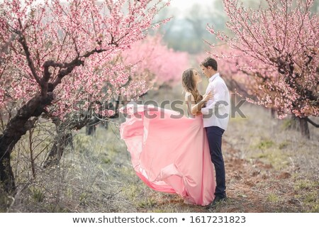 Romantic bridegroom kissing bride on forehead while standing against wall covered with pink flowers Stock photo © ElenaBatkova