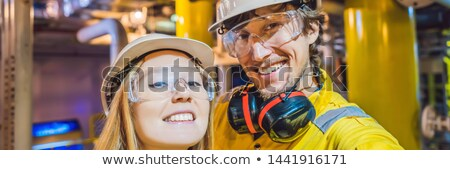 man and woman in a yellow work uniform glasses and helmet in an industrial environment oil platfo stock photo © galitskaya
