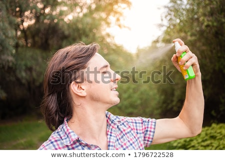 Stock photo: Man Spraying Anti Insect Deet Spray On His Arm