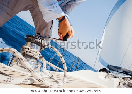 sailing crew member pulling rope on sailboat stock photo © boggy