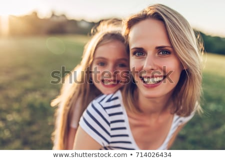 Young mother and her young daughter fun time together outdoors. Stock photo © Lopolo