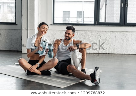 couple with bottles, exercise mat and towel in gym Stock photo © dolgachov