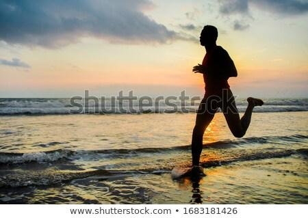 Man doing sports at the sea's, sunset Stock photo © galitskaya