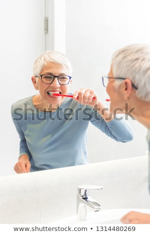 senior woman with toothbrush brushing her teeth Stock photo © dolgachov