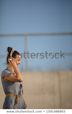 Pretty, young woman with headphones standing against concrete wall Stock photo © lightpoet