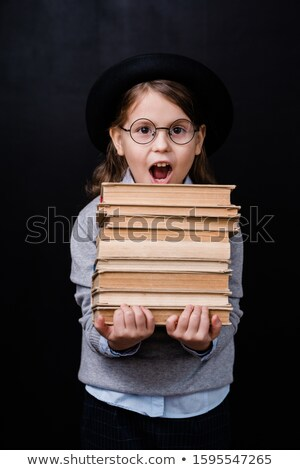 Excited elementary schoolgirl in hat and eyeglasses carrying stack of books Stock photo © pressmaster