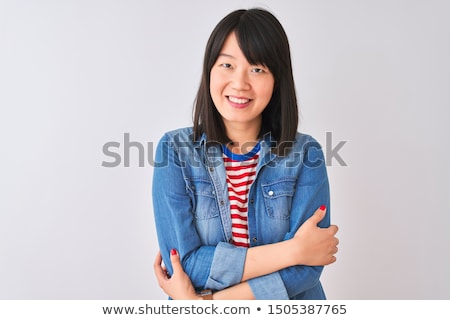 Portrait of a beautiful young woman wearing a denim shirt, touch stock photo © HASLOO