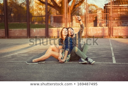 portrait of beautiful young couple sitting on ground in park rel stock photo © hasloo