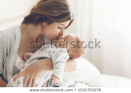 Happy mother kissing her newborn baby Stock photo © wavebreak_media