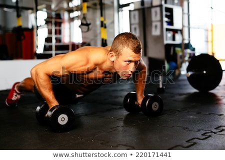 Gym man with dumbbells exercise crossfit Stock photo © lunamarina