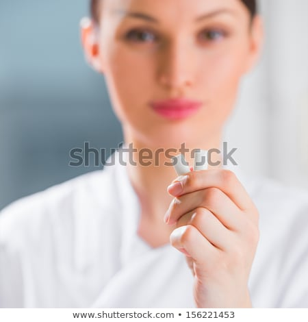 Stock photo: Young female dentist doctor holding chewing gum and smiling. Den