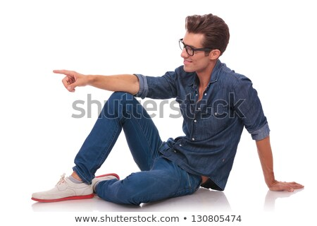 seated young casual man points to side stock photo © feedough
