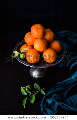 unripe green mandarin with leaves on a metal plate. Chiaroscuro with cloth and other tangerine in th Stock photo © faustalavagna