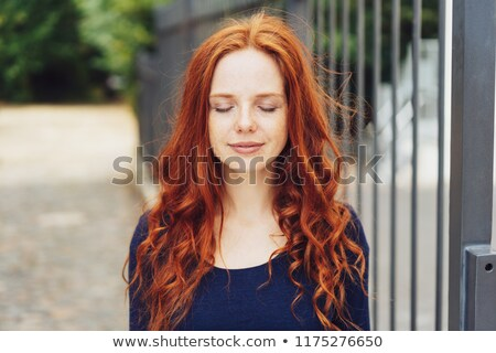 attractive young woman with closed eyes standing in the city stock photo © deandrobot
