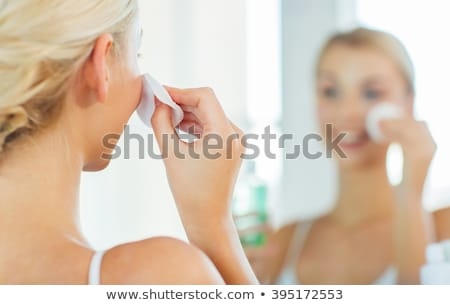 close up of woman cleaning face at bathroom stock photo © dolgachov