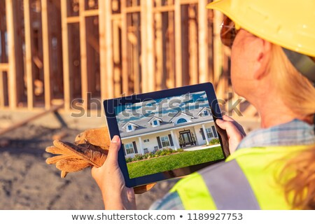 Female Construction Worker Reviewing House Photo on Computer Pad Stock photo © feverpitch
