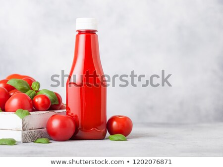Plastic container with tomato ketchup sauce with raw tomatoes on kitchen stone background. Stock photo © DenisMArt