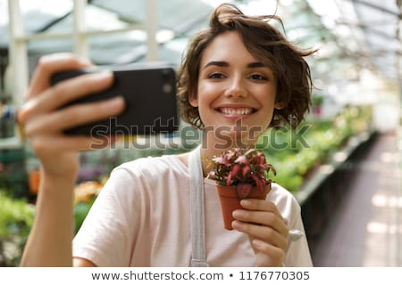 cute woman gardener standing over flowers plants in greenhouse showing peace gesture stock photo © deandrobot