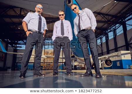 handsome man standing in front of aeroplane stock photo © konradbak