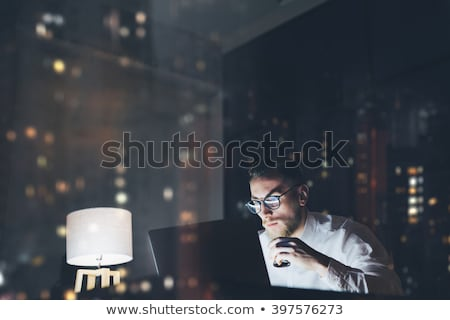 creative man with computer working at night office Stock photo © dolgachov