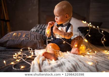 Bebê menino grinalda lâmpadas cama Foto stock © Stasia04