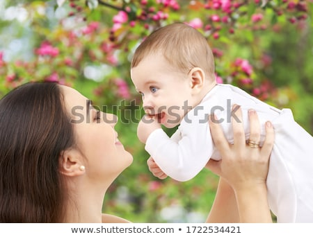 mother with baby over cherry blossom background Stock photo © dolgachov