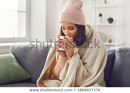 frozen young woman wearing sweater and hat stock photo © deandrobot