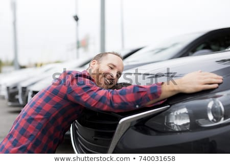 A Happy young man hugging his car outside of garage shop Stock photo © Lopolo