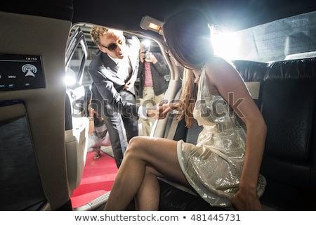 Woman getting out of limousine car Stock photo © Kzenon