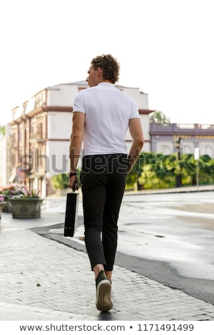 Back view of curly business man with briefcase walking Stock photo © deandrobot