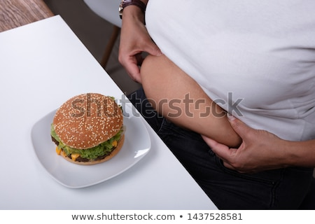 Woman Pinching Her Fatty Stomach With Hamburger On Table Stock photo © AndreyPopov