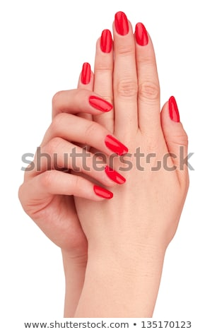 Beautiful female finger nails with red nail closeup on petals. P Stock photo © serdechny