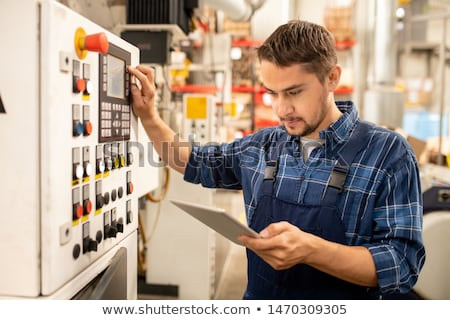 young factory technician looking through online instructions by control panel stock photo © pressmaster