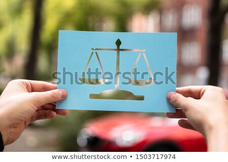 Hands Holding Paper With Cutout Law Scales Stock photo © AndreyPopov