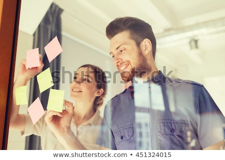 happy creative team at office glass board stock photo © dolgachov
