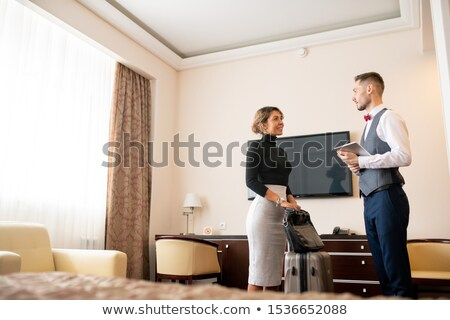 Young elegant porter with touchpad talking to pretty businesswoman with baggage Stock photo © pressmaster