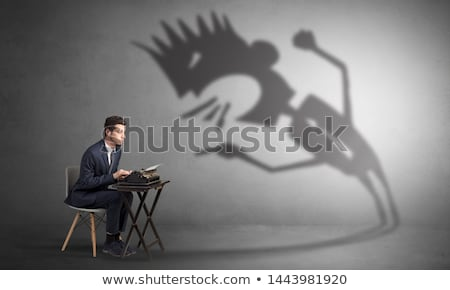 man working and he is afraid of a yelling shadow stock photo © ra2studio