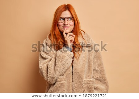 Dreamy redhaired European woman looks gladfully aside, smiles broadly, wears casual domestic clothes Stock photo © vkstudio