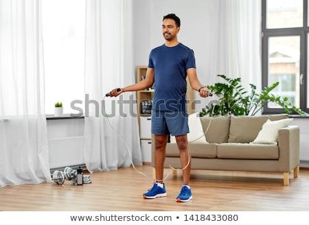 indian man exercising with jump rope at home Stock photo © dolgachov